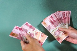 An Asian male hand is holding bunches of Indonesian Rupiah (IDR) Red 100,000 bank notes currency with green concrete wall and shadow background