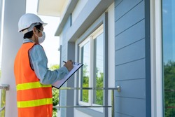 An Asian male inspector wears a white helmet. Inspectors check the structure of the house before handing it over to the customer or landlord. The concept of home inspection and construction.