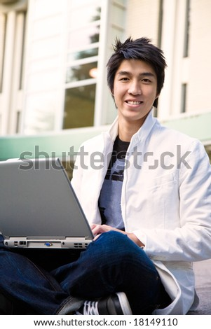 An asian male student working on his laptop
