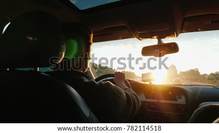 An Asian man drives a car along the highway, the setting sun shines in the windshield. Back view #782114518