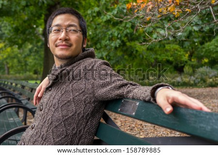 an asian man in his twenties relaxing on a bench in a park #158789885