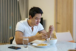 An Asian man is eating dinner alone at the dining table at night at home.