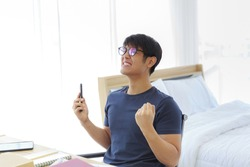 An Asian man is working in the bedroom, he gladly with a smartphone in his hand after receiving the good news.