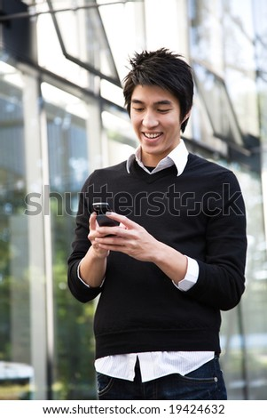An asian man texting on the cellphone