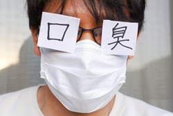 An Asian man wearing a mask. Translation: mouth, stinky.