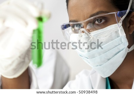 An Asian medical or scientific researcher or doctor looking at a test tube of green solution in a laboratory.