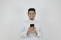 An Asian Muslim man wearing a white Muslim shirt or koko shirt and a black cap smiles while holding and looking his smartphone