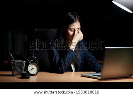 An Asian office worker is working overtime at the office. She has headache.