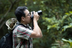 An asian senior photographer using millorless camera to took the photo, with green bokeh background. Traveller in scottish shirt took photo.