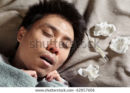 An Asian sick man, sleeping with thermometer showing high temperature