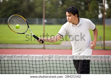 An asian tennis player hitting the ball - stock photo