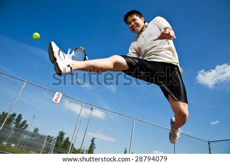 photo : An asian tennis player jumping in the air hitting a tennis ball