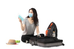 An Asian woman arranges a travel bag and prepares a mask to protect the coronavirus. White background.