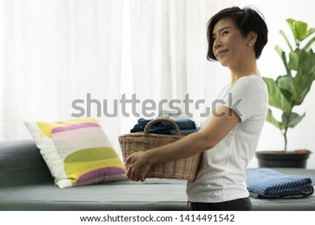 An asian woman carry a weaving bamboo laundry basket full of clean folded cloths and towels. Woman, Wife, Mom daily routine housework concept. #1414491542