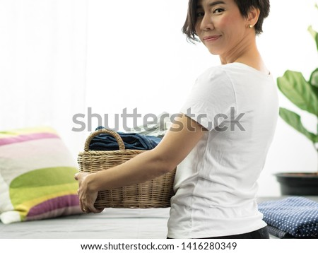 An asian woman carry a weaving bamboo laundry basket full of clean folded cloths and towels. Woman, Wife, Mom daily routine housework concept. #1416280349