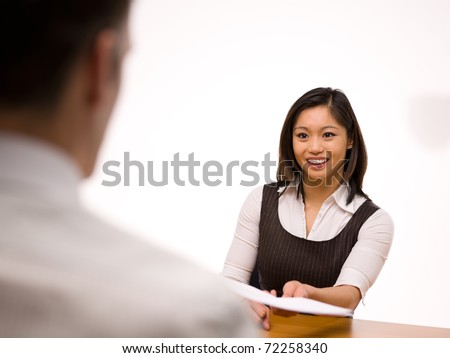 An asian woman giving her resume to a man at a job interview