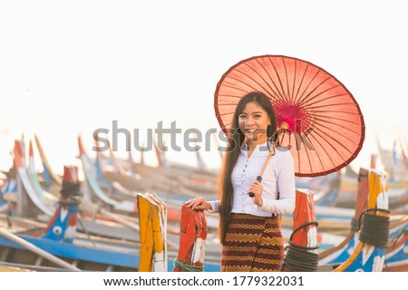 An Asian woman holding a red umbrella with a gondola. A young Burmese woman with a red umbrella on wooden boat at bridge in Asia.U-bein bridge, Mandalay, Myanmar. Сток-фото ©