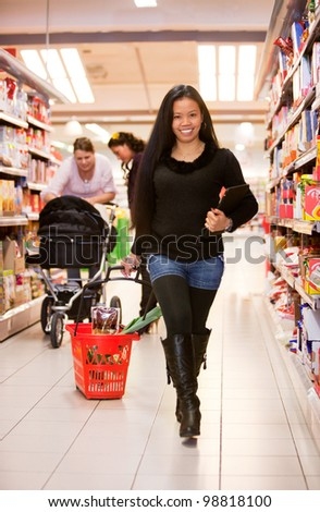 An asian woman in a grocery store with a basket