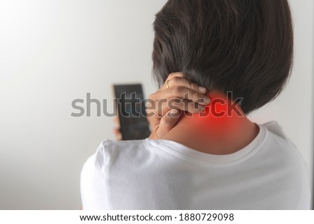 An Asian woman is looking at her mobile phone.She put a handle on the back of her neck because she was in pain from looking at the cell phone too much. Foto stock ©