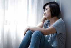 An Asian woman is staring outside the window. She has symptoms of depression, stress and gloom.
