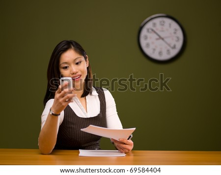 An asian woman paying bills online using a smartphone