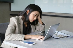 An asian woman sitting at desk looking at laptop screen with thinking and stress, eye bow fold together and hand overhead.