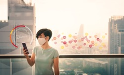 An asian woman use her smartphone application checking real-time Air Quality at the balcony outside the building. The data show the air in Bangkok city is very poor and unhealthy to breath. PM 2.5