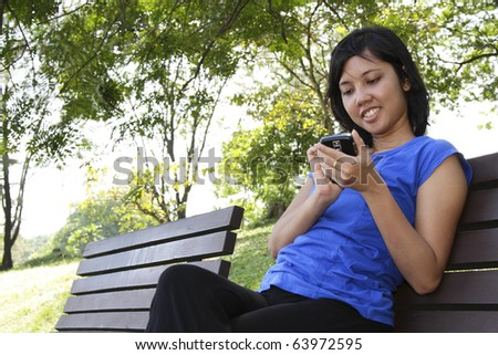An Asian woman using her cellphone at a park