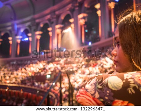 An asian woman watching a west end show with blurred crowds of seated people in background #1322963471