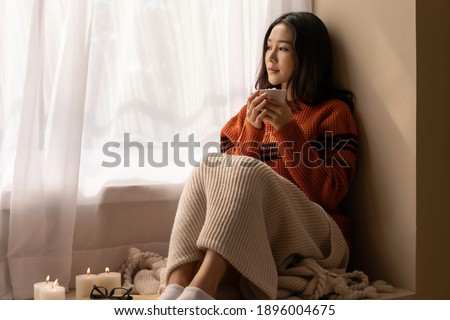 An Asian woman wearing a sweater inhaled the scent and drank the winter morning coffee. She looked at the view from the large window on vacation. Stockfoto ©