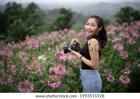 An asian woman with freckles holding camera, looking and smilling to camera with happiness on pink field blurred background.