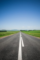An asphalt road among meadows leading to the mountains on the horizon. Beautiful summer landscape with blue skies, greenery and highway. Minimalism, transport links, travel concept.
