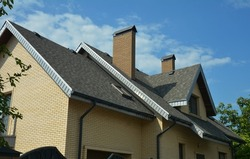 An asphalt shingled roof with skylights, attic windows, chimneys, fascias, and a roof gutter. A close-up of a gray double-pitched roof covered with dimensional asphalt roofing shingles.