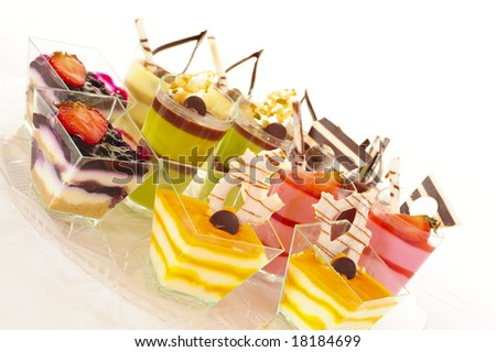 An assortment of colorful mousse desserts in cups.