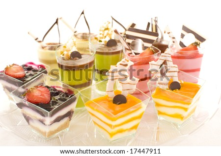 An assortment of colorful mousse desserts in cups, on a white background.