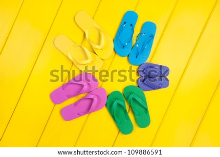 An assortment of colorful rubber flip flops in a circular pattern on a wooden, yellow pool deck.