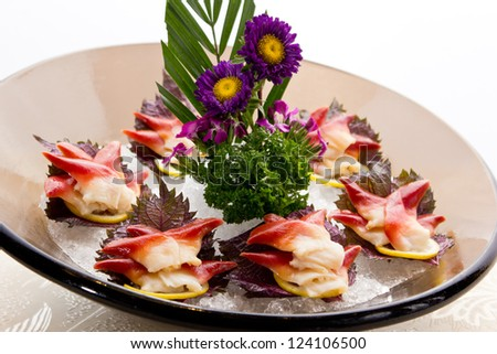 An assortment of different types of sashimi served on a delicate set up.