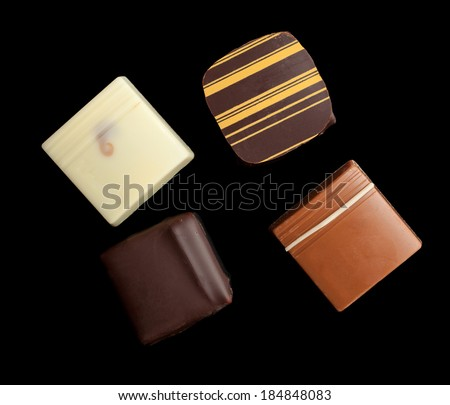 An assortment of fine chocolates in white, dark, and milk chocolate on black background