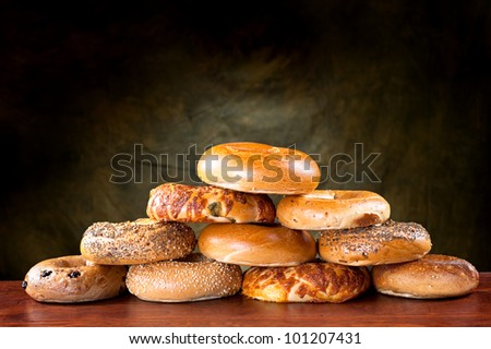 An assortment of flavored, seasoned breakfast bagels against a moody, green backdrop.