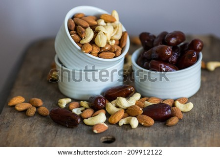 An assortment of healthy nuts in a bowl : almond, cashew, dates and hazelnut, making a healthy snack alternative