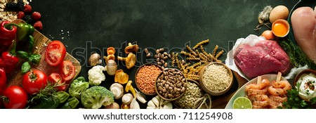 An assortment of healthy, organic, paleo harvest produce, legumes, meats and vegetables on a dark grey background with copy space in a panoramic orientation.