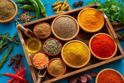 An assortment of herbs and spices as ingredients towards an Indian or Asian  Cuisine, on a blue background