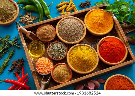 An assortment of herbs and spices as ingredients towards an Indian or Asian  Cuisine, on a blue background Photo stock ©