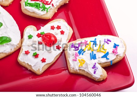 An assortment of homemade Christmas cookies decorated and in the shape of mittens.