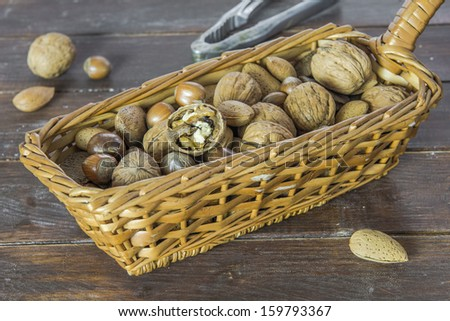 An assortment of nuts in a basket on wooden table