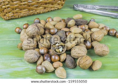 An assortment of nuts on green wooden table