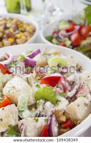 An assortment of salads on a buffet table. Potato salad, bean salad and fresh mixed salad arranged on a white table with glasses, cutlery and plates. Focus on potato salad. - stock photo