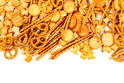An assortment of salt crackers, sticks, pretzels, and goldfishes, shot from above on a white background with copy space. Salty party snacks mix with a place for text