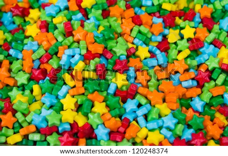 An assortment of shiny, brightly colored hard candy-coated stars which have a plastic look & feel to them fills the entire frame with focus at the center of the image & falling away towards the edges
