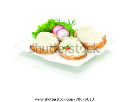 an assortment of spread cheese, mixed with herbs, on three slices of sesame baguette, decorated with fresh vegetables